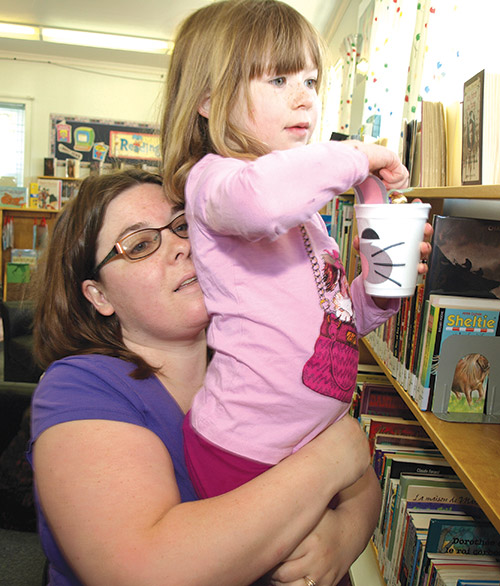 Jennifer Breault gave daughter Kendall Morgan a lift as the four-year-old searched for Easter eggs at the Haileybury library. The Sudbury family, in Temiskaming Shores on the holiday weekend visiting relatives, joined the crowd of chocolate hunters. (Staff photo by Diane Johnston)